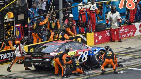 Crew members perform a pit stop on driver Martin Truex Jr.'s car during the NASCAR Cup Series auto race at Charlotte Motor Speedway in Charlotte, N.C., Sunday, May 27, 2018. (AP Photo/Mike McCarn)