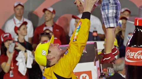 Kyle Busch tosses his son Brexton in the air as he celebrates after winning the NASCAR Cup Series auto race at Charlotte Motor Speedway in Charlotte, N.C., Sunday, May 27, 2018. (AP Photo/Chuck Burton)