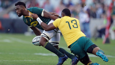 FILE - In this Sept. 30, 2017 file photo South Africa's Siya Kolisi, left, is tackled by Australia's Tevita Kuridrani, during a Rugby Championship match between South Africa and Australia, at the Free State Stadium in Bloemfontein, South Africa. Kolisi has become the first black player to be appointed captain of South Africas test rugby team, it was reported on Monday, May 28, 2018. Kolisi has been named captain for the series against England next month. (AP Photo/Themba Hadebe, File)