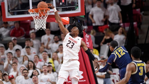 Maryland forward Bruno Fernando (23) dunks against Michigan guard Muhammad-Ali Abdur-Rahkman (12) and guard Zavier Simpson (3) during the first half of an NCAA college basketball game, Saturday, Feb. 24, 2018, in College Park, Md. (AP Photo/Nick Wass)