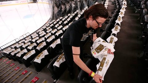 Jared Lang places towels in a section of seats at the T-Mobile Arena prior to Game 1 of the NHL Stanley Cup Finals hockey game between the Vegas Golden Knights and the Washington Capitals, Monday, May 28, 2018, in Las Vegas. (AP Photo/Ross D. Franklin)