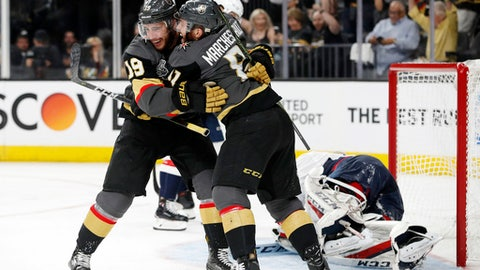 Vegas Golden Knights right wing Reilly Smith, left, celebrates his goal with center Jonathan Marchessault, center, as Washington Capitals goaltender Braden Holtby lays on the ice during second period in Game 1 of the NHL hockey Stanley Cup Finals Monday, May 28, 2018, in Las Vegas. (AP Photo/John Locher)