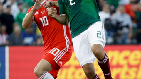 Mexico's Oswaldo Alanis, right, heads the ball away from Wales' Aaron Ramsey during the first half of a soccer match, Monday, May 28, 2018, in Pasadena, Calif. (AP Photo/Chris Carlson)