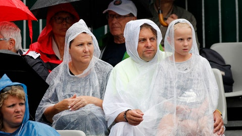 Spectators wearing rain coats watch Bethanie Mattek-Sands of the U.S. playing Sweden's Johanna Larsson during their first round match of the French Open tennis tournament at the Roland Garros stadium, Tuesday, May 29, 2018 in Paris. (AP Photo/Christophe Ena)