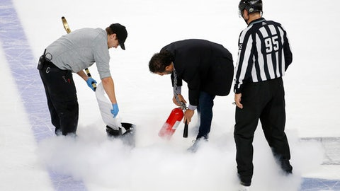 Ice maintenance crew members repair the ice with a fire extinguisher as linesman Jonny Murray watches during the second period in Game 1 of the NHL hockey Stanley Cup Finals between the Vegas Golden Knights and the Washington Capitals Monday, May 28, 2018, in Las Vegas. (AP Photo/Ross D. Franklin)