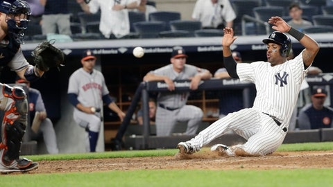 New York Yankees' Miguel Andujar slides home with the winning run on a single by Gleyber Torres as Houston Astros catcher Max Stassi waits for the throw during the 10th inning of a baseball game Tuesday, May 29, 2018, in New York. (AP Photo/Frank Franklin II)