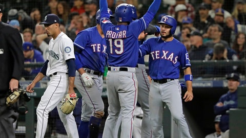 Seattle Mariners closing pitcher relief pitcher Edwin Diaz, left, walks back to the mound after covering home as Texas Rangers' Jurickson Profar (19) celebrates with teammates as he scored on a three-run double hit by Rougned Odor during the ninth inning of a baseball game Tuesday, May 29, 2018, in Seattle. (AP Photo/Ted S. Warren)