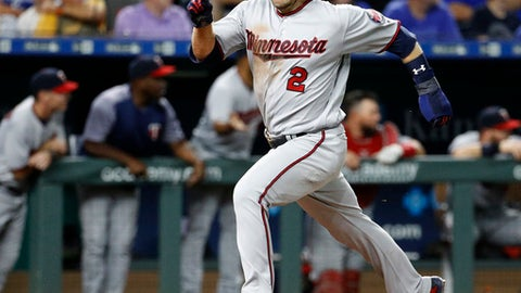 Minnesota Twins' Brian Dozier runs home to score on a two-run double by Miguel Sano during the sixth inning of a baseball game against the Kansas City Royals on Wednesday, May 30, 2018, in Kansas City, Mo. (AP Photo/Charlie Riedel)