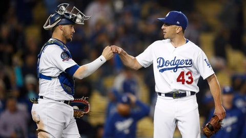 Los Angeles Dodgers relief pitcher Pat Venditte, right, and catcher Yasmani Grandal celebrate the team's 8-2 win against the Philadelphia Phillies in a baseball game Wednesday, May 30, 2018, in Los Angeles. (AP Photo/Jae C. Hong)