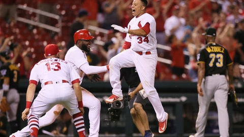 St. Louis Cardinals' Yairo Munoz (34) is greeted by teammates, including Marcell Ozuna, second from left, and Matt Carpenter, left, at home plate after he hit a walk-off three-run home run off Pittsburgh Pirates pitcher Felipe Vazquez (73) during the ninth inning of a baseball game at Busch Stadium on Thursday, May 31, 2018, in St. Louis. (Chris Lee/St. Louis Post-Dispatch via AP)