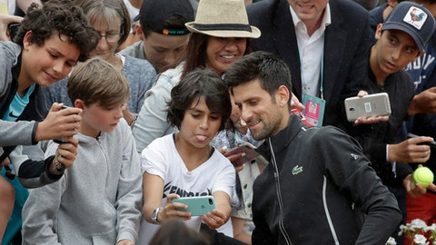 Serbia's Novak Djokovic poses with spectators after winning his third round match of the French Open tennis tournament against Spain's Roberto Bautista Agut in four sets 6-4, 6-7 (6-8), 7-6 (7-4), 6-2, at the Roland Garros stadium in Paris, France, Friday, June 1, 2018. (AP Photo/Alessandra Tarantino)