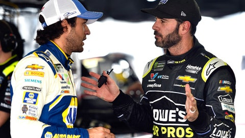 Jimmie Johnson, right, talks to Chase Elliott in the garage area during practice for Sunday's NASCAR Cup Series Pocono 400 auto race, Friday, June 1, 2018, in Long Pond, Pa. (AP Photo/Derik Hamilton)