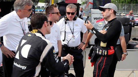 Team Penske drivers Will Power, right, and Simon Pagenaud talk with Chevrolet engineers after a practice session, Friday, June 1, 2018 for the IndyCar Detroit Grand Prix auto racing doubleheader on Belle Isle in Detroit this weekend. (AP Photo/Carlos Osorio)