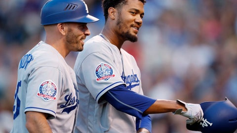 Los Angeles Dodgers third base coach Chris Woodward, left, congratulates Dennis Santana, who drove in two runs with a double off Colorado Rockies starting pitcher Tyler Anderson during the fourth inning of a baseball game Friday, June 1, 2018, in Denver. (AP Photo/David Zalubowski)