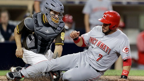 The Cincinnati Reds' Eugenio Suarez (7) scores off a single by Jose Peraza as San Diego Padres catcher Raffy Lopez, left, is late with the tag during the seventh inning of a baseball game Friday, June 1, 2018, in San Diego. (AP Photo/Gregory Bull)