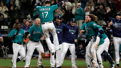 Seattle Mariners' Mitch Haniger (17) leaps onto home plate after he hit a walk-off home run against the Tampa Bay Rays during the 13th inning of a baseball game, Friday, June 1, 2018, in Seattle. The Mariners won 4-3 in 13 innings. (AP Photo/Ted S. Warren)