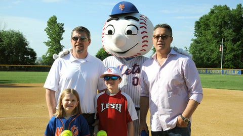 In this photo provided the Mets, Kendall and Nick Forde, front row, pose with their father John Forde, left, top row, Mr. Met, and former Mets pitcher Ron Darling, right top row, Saturday, June 2, 2018, at Shannon Forde Field, in Little Ferry, N.J. Darling was among those who attended the first softball games played at Shannon Forde Field, named for the New York public relations official who died of breast cancer in March 2016.  The field in Little Ferry, New Jersey, was dedicated a year ago and opened Saturday.  (Steve Cutler/Mets via AP)