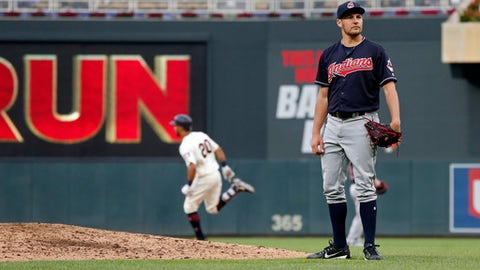 Minnesota Twins' Eddie Rosario, left, rounds the bases on his two-run home run off Cleveland Indians' pitcher Trevor Bauer, right, in the third inning of a baseball game Saturday, June 2, 2018, in Minneapolis. (AP Photo/Jim Mone)