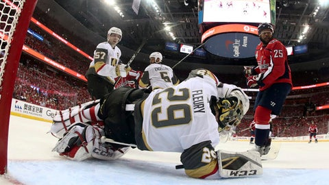 Vegas Golden Knights goaltender Marc-Andre Fleury falls to the ice after Washington Capitals forward Devante Smith-Pelly (25) collided with him during the first period in Game 3 of the NHL hockey Stanley Cup Final, Saturday, June 2, 2018, in Washington. Smith-Pelly was called for a goaltender interference and there was no goal on the play. (Bruce Bennett/Pool Photo via AP)