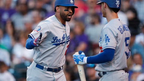 Los Angeles Dodgers' Matt Kemp, left, celebrates with Cody Bellinger while passing the on-deck circle after hitting a two-run home run off Colorado Rockies relief pitcher Bryan Shaw in the seventh inning of a baseball game Saturday, June 2, 2018, in Denver. (AP Photo/David Zalubowski)