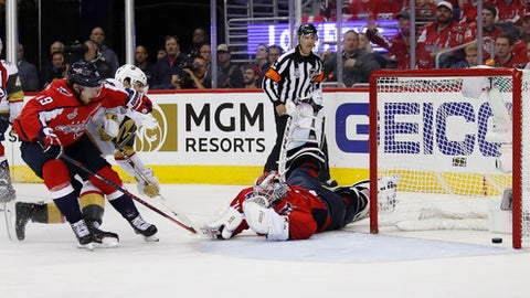 Washington Capitals goaltender Braden Holtby, right cannot stop a shot by Vegas Golden Knights forward Tomas Nosek, center, of the Czech Republic, as Capitals forward Nicklas Backstrom, left, of Sweden, defends during the third period in Game 3 of the NHL hockey Stanley Cup Final, Saturday, June 2, 2018, in Washington. (AP Photo/Alex Brandon)