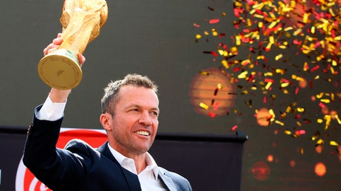Former German soccer star Lothar Matthaus holds up the trophy during a ceremony to welcome the FIFA World Cup trophy at Manezh Square in Moscow, Russia, Sunday, June 3, 2018. (Kirill Zykov/Moscow News Agency photo via AP)