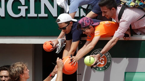 Germany's Alexander Zverev signs autographs as he celebrates winning his fourth round match of the French Open tennis tournament against Russia's Karen Khachanov in five sets 4-6, 7-6 (7-4), 2-6, 6-3, 6-3, at the Roland Garros stadium in Paris, France, Sunday, June 3, 2018. (AP Photo/Alessandra Tarantino)