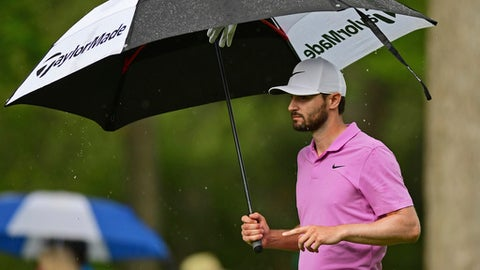 Kyle Stanley walks with an umbrella on the eighth hole during the final round of the Memorial golf tournament Sunday, June 3, 2018, in Dublin, Ohio. (AP Photo/David Dermer)