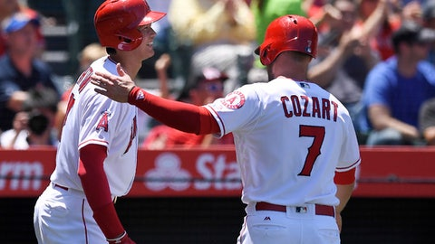 Los Angeles Angels' Shohei Ohtani, left, of Japan, smiles after he and Zack Cozart, right, scored on a double by Luis Valbuena during the second inning of a baseball game against the Texas Rangers, Sunday, June 3, 2018, in Anaheim, Calif. (AP Photo/Mark J. Terrill)