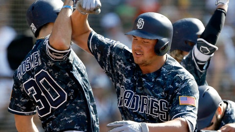 San Diego Padres' Hunter Renfroe, center, gets congratulations at the plate from Eric Hosmer, left, after hitting a grand slam home run against the Cincinnati Reds during the fifth inning of a baseball game in San Diego, Sunday, June 3, 2018. (AP Photo/Alex Gallardo)