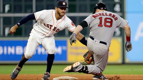 Boston Red Sox's Mitch Moreland (18) is tagged out by Houston Astros shortstop Carlos Correa (1) while trying to stretch a single into a double during the eighth inning of a baseball game Sunday, June 3, 2018, in Houston. (AP Photo/David J. Phillip)