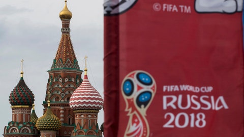 A flag with the logo of the World Cup 2018 on display with the St. Basil's Cathedral in the background, in Moscow, Russia, Monday, June 4, 2018. (AP Photo/Pavel Golovkin)