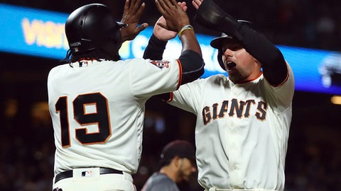 San Francisco Giants' Joe Panik, right, celebrates with Alen Hanson (19) after both scored against the Arizona Diamondbacks in the fourth inning of a baseball game Monday, June 4, 2018, in San Francisco. Both scored on a double by Giants' Buster Posey. (AP Photo/Ben Margot)