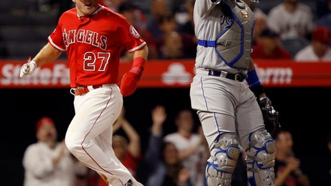 Los Angeles Angels' Mike Trout, left, scores behind Kansas City Royals catcher Salvador Perez on a single by Albert Pujols during the sixth inning of a baseball game in Anaheim, Calif., Monday, June 4, 2018. Los Angeles won, 9-6. (AP Photo/Alex Gallardo)