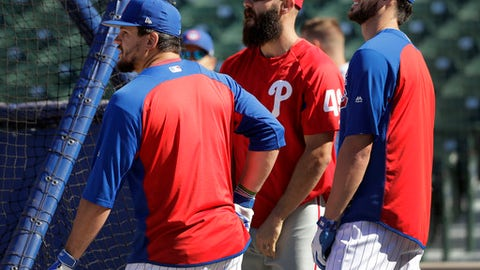 Philadelphia Phillies' Jake Arrieta, center, talks with former teammates Chicago Cubs' Kyle Schwarber, left, and Kris Bryant during the Cubs' batting practice before a baseball game Tuesday, June 5, 2018, in Chicago. (AP Photo/Charles Rex Arbogast)