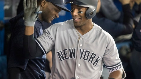 New York Yankees' Miguel Andujar is congratulated in the dugout after he hit a grand slam against the Toronto Blue Jays during the seventh inning of a baseball game Tuesday, June 5, 2018, in Toronto. (Fred Thornhill/The Canadian Press via AP)