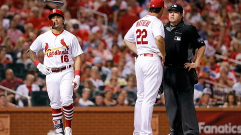 St. Louis Cardinals' Kolten Wong, left, flips his bat as he walks away after being called out by home plate umpire Doug Eddings, right, on batter interference, as Cardinals manager Mike Matheny pleads Wong's case during the sixth inning of the team's baseball game against the Miami Marlins on Tuesday, June 5, 2018, in St. Louis. (AP Photo/Jeff Roberson)
