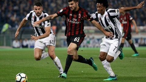 FILE - In this May 9, 2018 file photo, AC Milan's Patrick Cutrone, center, is challenged by Juventus' Andrea Barzagli, left, and Juventus' Juan Cuadrado during the Italian Cup final soccer match between Juventus and AC Milan, at the Rome Olympic stadium. The Italian league told The Associated Press on Wednesday, June 6, 2018, that the first match of the series will be held in January, between Serie A champion Juventus and Italian Cup finalist AC Milan. (AP Photo/Gregorio Borgia, file)