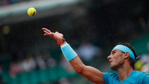 Spain's Rafael Nadal serves in light rain just before his quarterfinal match of the French Open tennis tournament against Argentina's Diego Schwartzman got interrupted for the second time at the Roland Garros stadium in Paris, France, Wednesday, June 6, 2018. (AP Photo/Christophe Ena)