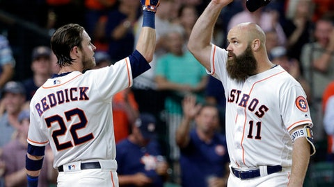 Houston Astros' Josh Reddick (22) and designated hitter Evan Gattis (11) tap helmets after scoring on a home run by Gattis during the fourth inning of the team's baseball game against the Seattle Mariners on Wednesday, June 6, 2018, in Houston. (AP Photo/Michael Wyke)