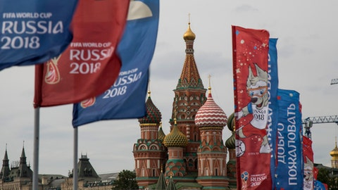 FILE - In this June 4, 2018, file photo, flags with the logo of the World Cup 2018 on display with the St. Basil's Cathedral in the background, in Moscow, Russia. If you're looking for the favorite when the World Cup opens in Russia, it's Brazil. Spain will be the losing finalist. If real outsiders are of interest, two to keep in mind might be Latin American teams Colombia and Peru. (AP Photo/Alexander Zemlianichenko, File)