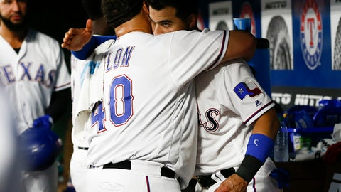 Texas Rangers' Bartolo Colon (40) is embraced by Robinson Chirinos, right, as he arrives in the dugout following the fifth inning of the team's baseball game against the Oakland Athletics, Wednesday, June 6, 2018, in Arlington, Texas. (AP Photo/Jim Cowsert)