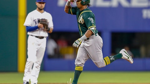 Oakland Athletics' Khris Davis gestures to his team's bench, while passing Texas Rangers third baseman Isiah Kiner-Falefa as he rounds the bases on his two-run home run during the fifth inning of a baseball game Wednesday, June 6, 2018, in Arlington, Texas. (AP Photo/Jim Cowsert)