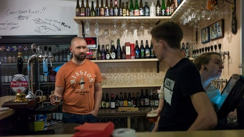 FILE - In this Friday, May 22, 2015 file photo, Stanislav Obraztsov, left, speaks to his colleagues at his craft beer bar in Moscow, Russia. For many fans of food and football, a World Cup in Russia is unfamiliar territory. Russian cuisine has a reputation for being stodgy, unimaginative fare. While that may have been true for many in the days of Soviet supply shortages, a new generation of Russian in the World Cups host cities mix together influences from across Europe and Asia. (AP Photo/Alexander Zemlianichenko, File)