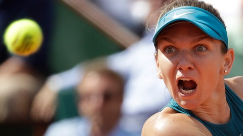 Romania's Simona Halep eyes the ball as she returns a shot against Spain's Garbine Muguruza during their semifinal match of the French Open tennis tournament at the Roland Garros stadium in Paris, France, Thursday, June 7, 2018. (AP Photo/Alessandra Tarantino)