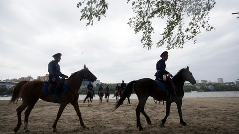 In this photo taken on Sunday, May 13, 2018, Don Cossacks practice on the bank of the Don river near the World Cup stadium before the Russian premier league soccer match between Rostov and Ural, in Rostov-on-Don, Russia. Russia plans to deploy thousands of Cossacks to guard the World Cup, but the traditional paramilitary groups face criticism for their strident nationalism and attacks on protesters. (AP Photo/Pavel Golovkin)