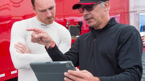 Actor Michael Fassbender, left, speaks to his driving coach as he prepares for the Ferarri Challenge practice at the Formula One Canadian Grand Prix auto race in Montreal, Friday, June 8, 2018. (Ryan Remiorz/The Canadian Press via AP)