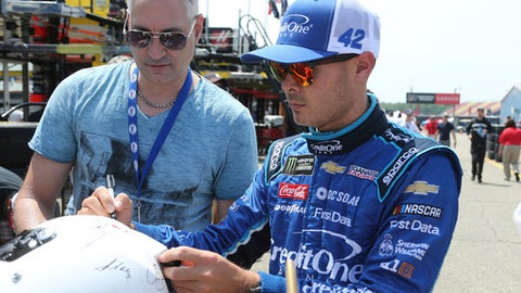 NASCAR driver Kyle Larson signs autographs after practice for the NASCAR Cup Series auto race in Brooklyn, Mich., Fruday, June 8, 2018.  (AP Photo/Bob Brodbeck)