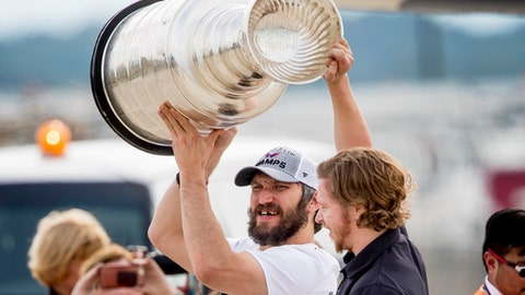 Washington Capitals left wing Alex Ovechkin, left, of Russia,, and center Nicklas Backstrom, of Sweden, right, hold up the Stanley Cup as the Capitols arrive at Dulles International Airport in Sterling, Va., Friday, June 8, 2018, the day after defeating the Vegas Golden Knights in Game 5 of the NHL hockey Stanley Cup Finals. (AP Photo/Andrew Harnik)