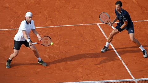 Austria's Oliver Marach, left, and Croatia's Mate Pavic, right, play a shot in the men's doubles final match of the French Open tennis tournament against France Pierre-Hughes Herbert and Nicolas Mahut at the Roland Garros stadium in Paris, France, Saturday, June 9, 2018. (AP Photo/Michel Euler)